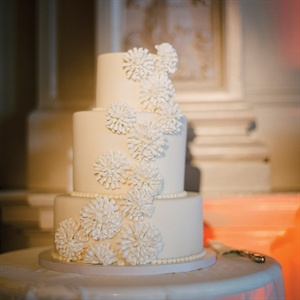 The ivory cake was topped with pearl piping and sculpted fondant designs to match Amy's dress.