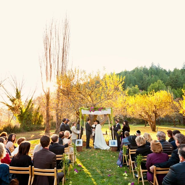 The couple wed in an orchard under a floral-decorated huppah.