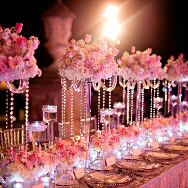 Jeweled stephanotis in low, mirrored boxes provide the base for this multilevel tablescape that feels fit for royalty. Long tables evoking a regal past are combined with modern elements like sleek, jewel-draped candelabras, while timeless arrangements of white hydrangeas, pink, blush and cream roses, white stock and pink tulips span the ages. Candl ...