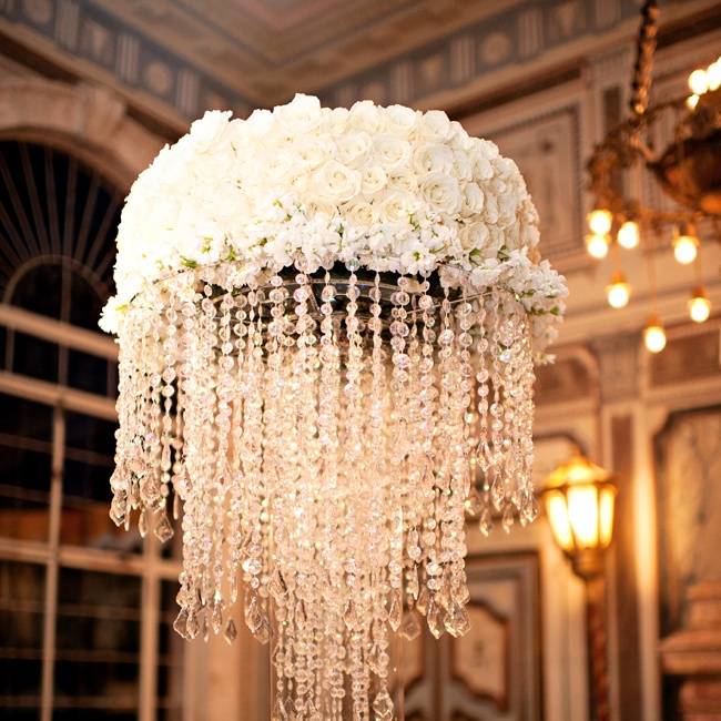 Contemporary elements can make a historic venue's decor -- like this antique chandelier -- look current. Lush white flowers and hanging crystals create a sparkling, textured effect that adds a modern twist to Miami's Vizcaya Museum and Gardens.