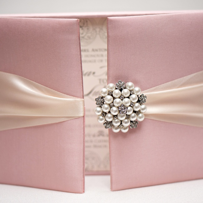 Instead of a simple paper suite, dress your wedding invitations up in a satin box with a pearl and crystal brooch clasp. Guests get a surprise inside -- it's like unwrapping a gift!