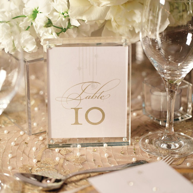 Elegant white-and-gold numbers topped tables.