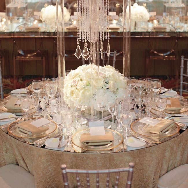 Clear modern stands were draped with crystals. Below rested all-white centerpieces and a mirrored tabletop.