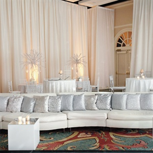 A modern-chic lounge area was set up with plush pillows and white couches.