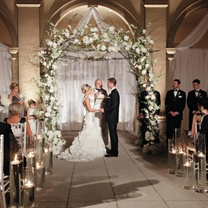 The couple wed beneath a romantic altar woven with peonies and hydrangeas.