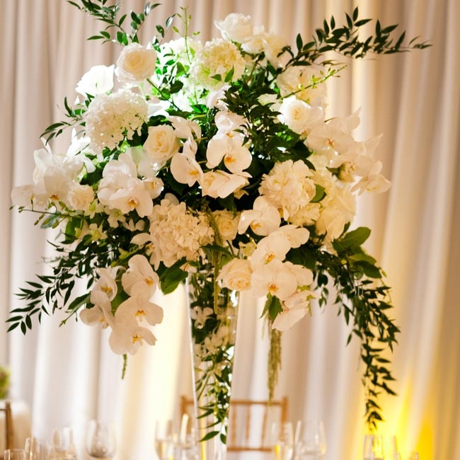 Tall glass vases were filled with white hydrangeas, peonies, roses and hanging green amaranthus.