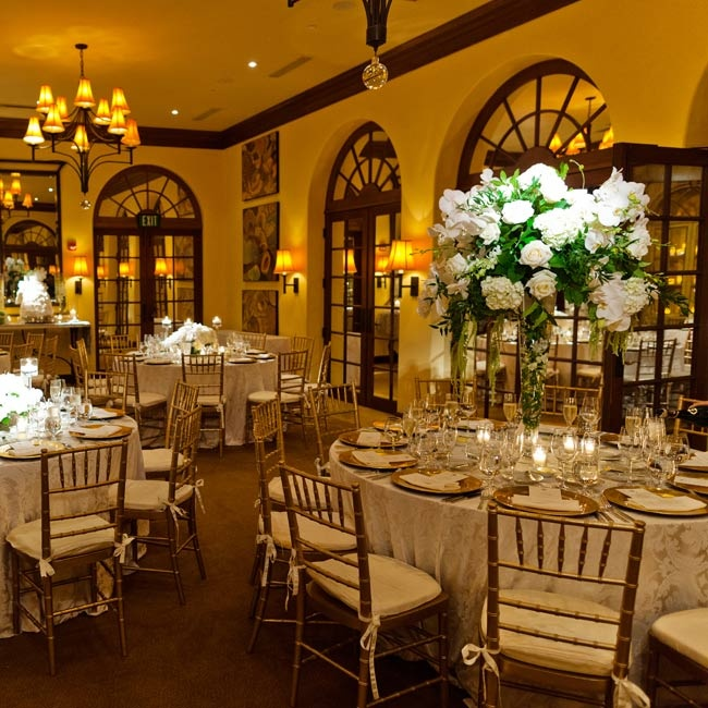 For a romantic vibe, gold chiavari chairs surrounded tables draped in ivory satin brocade linens.
