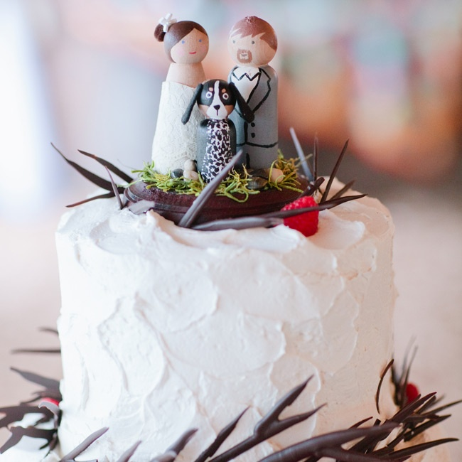 The couple's buttercream-frosted cake was decorated with branches around each tier, plus fresh raspberries.