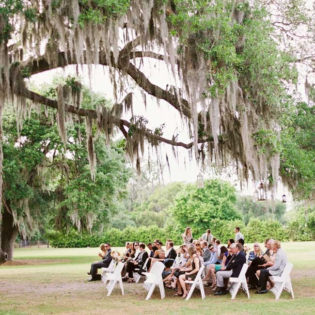 All the wedding guests sat beneath a giant oak tree. A few lanterns hung from it for a romantic, vintage effect.