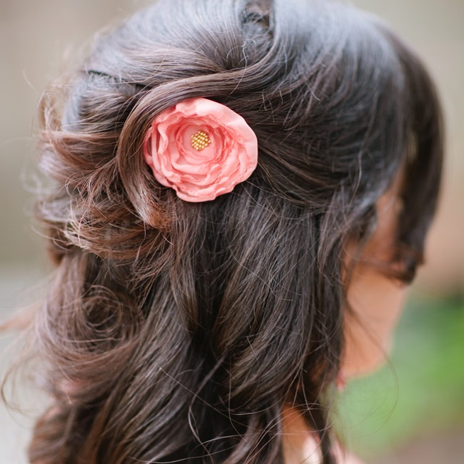 One of the bridesmaids wore her hair down with a coral-colored flower hairpin.