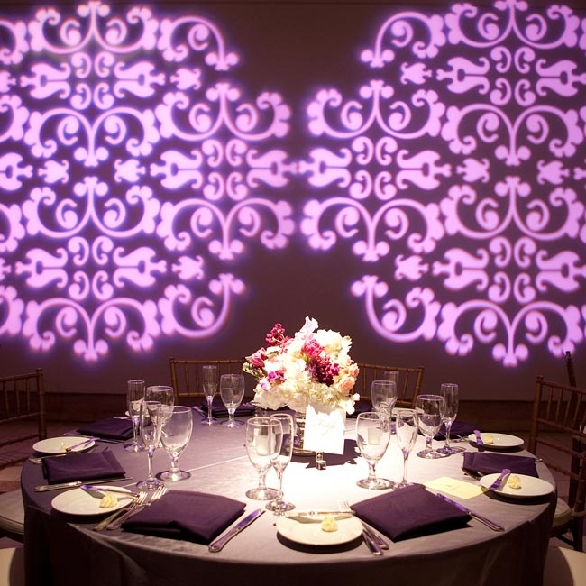 To coordinate with the rest of the day's décor, the couple backlit the reception with a purple-damask gobo.