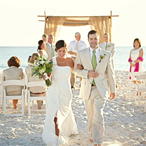 The couple wed on a private beach under a burlap-draped bamboo-pole arbor.
