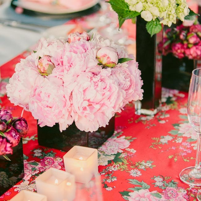 The table runners were fashioned after red kimonos. They were topped with various blooms housed in sleek black vases.