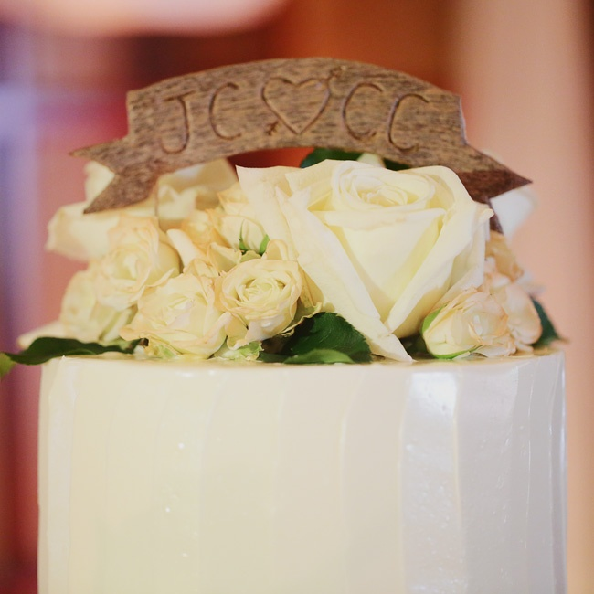 A wooden banner, with the couple's initials carved into it, topped the cake.