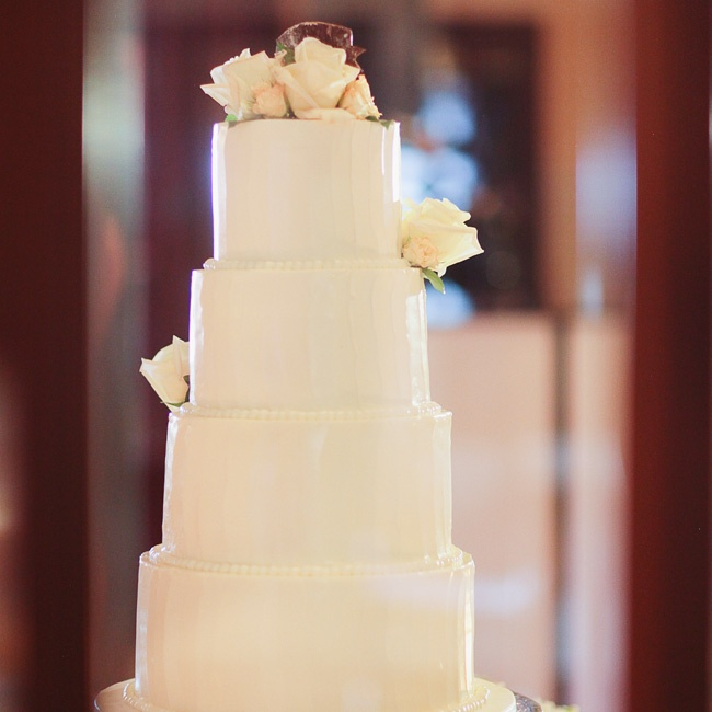 The sleek white cake was adorned with fresh roses.