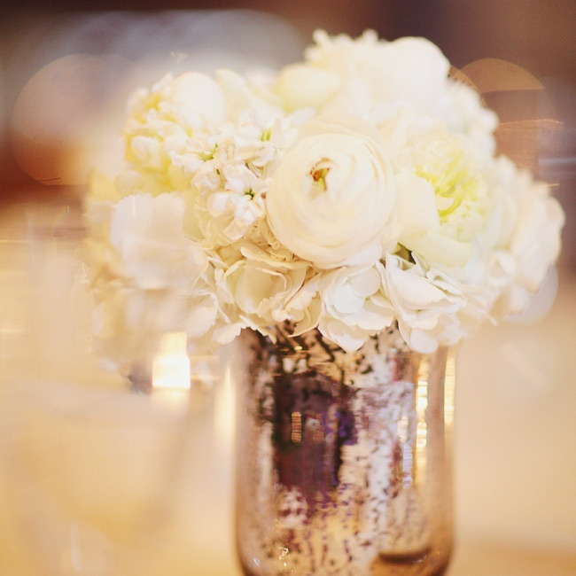 White hydrangeas and peonies were displayed in vintage-looking mercury-glass vases.
