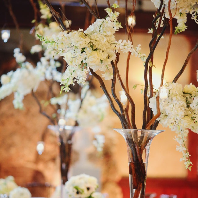 Tall trumpet vases were filled with dragonwood branches and white blooms.