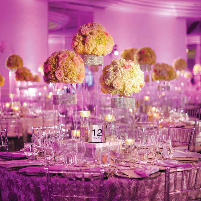Glass stands were topped with pink and white flowers.