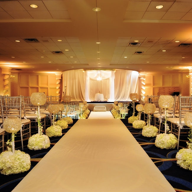 White floral poms and crystal globes lined the aisle.