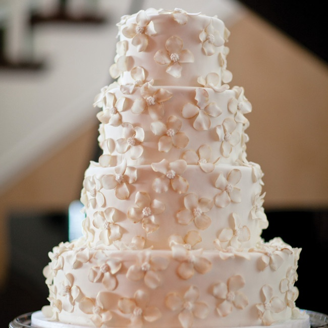 The four-tiered fondant confection was covered in gold-dusted sugar flowers and displayed on a silver stand.