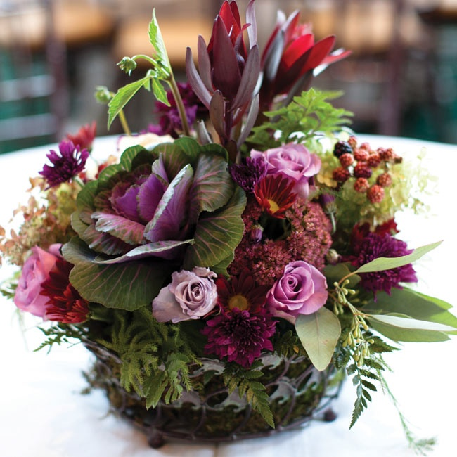 Low wire baskets of purple kale, dahlias, gerbera daisies, raspberries, spray roses and greenery topped some of the reception tables.