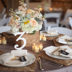 On some of the tables, peach peonies, lamb's ear, hydrangeas and craspedia filled white ceramic vases.