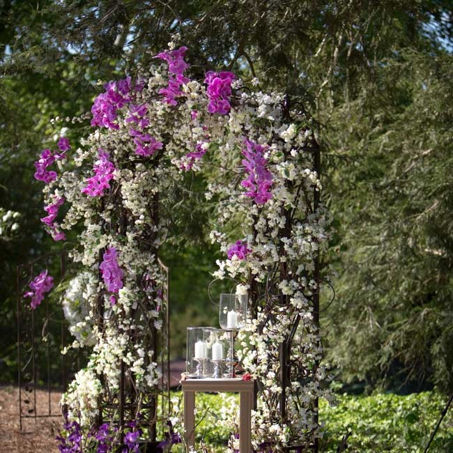 The couple exchanged vows outdoors under a white and purple flower-decorated arbor.