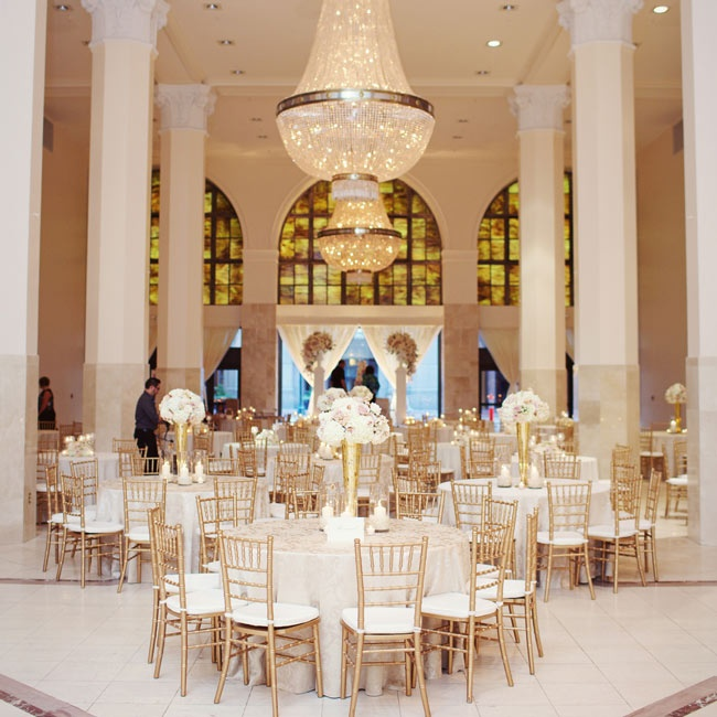 Large crystal chandeliers hung over tall gold vases filled with white-and-blush floral arrangements.