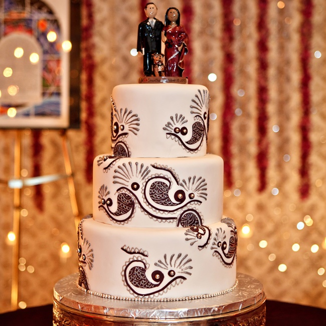 The creative and custom cake topper was a humorous likeness of Shwetha in a purple sari holding a toothbrush, Jeff in his tux and yamulke holding a calculator, and their little yorkie, Macgyver.