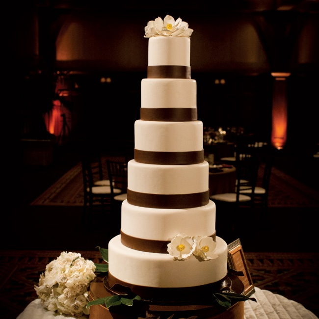 The six-tiered ivory cake was wrapped with brown ribbon and topped with delicate sugar flowers.
