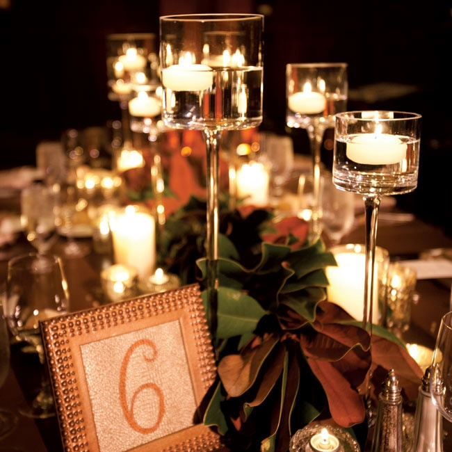 Glass vases holding floating candles added romance to the rustic tablescapes.