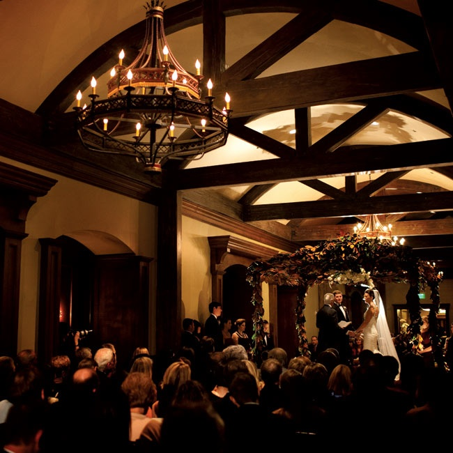 The couple wed indoors beneath a magnolia-covered canopy.
