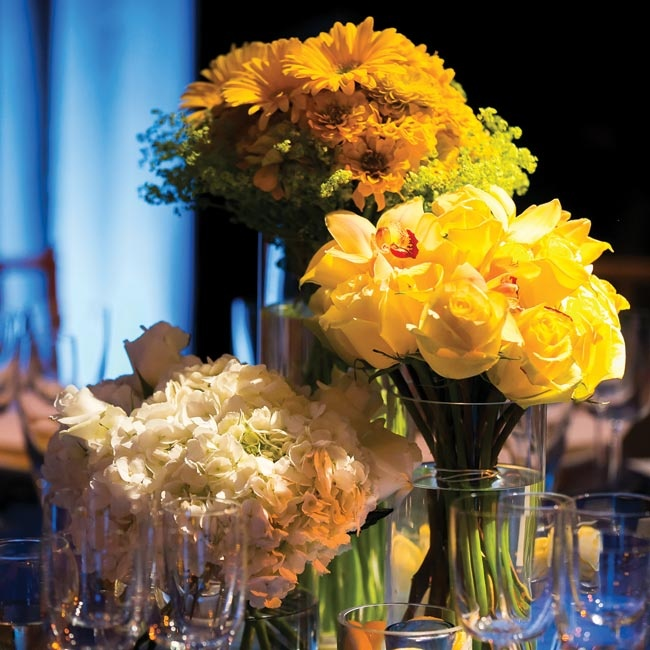 Round tables were topped with glass vases of varying heights and blooms. In smaller vases, candles illuminated lemon slices.