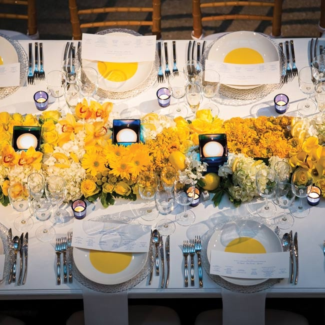 The rectangular tables boasted a lush mix of yellow and white flowers, whole and cut lemons, and square cobalt vases.