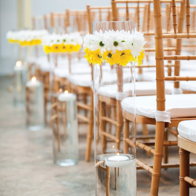 Tall glass cylinders with floating votives and bright daisies lined the aisle.