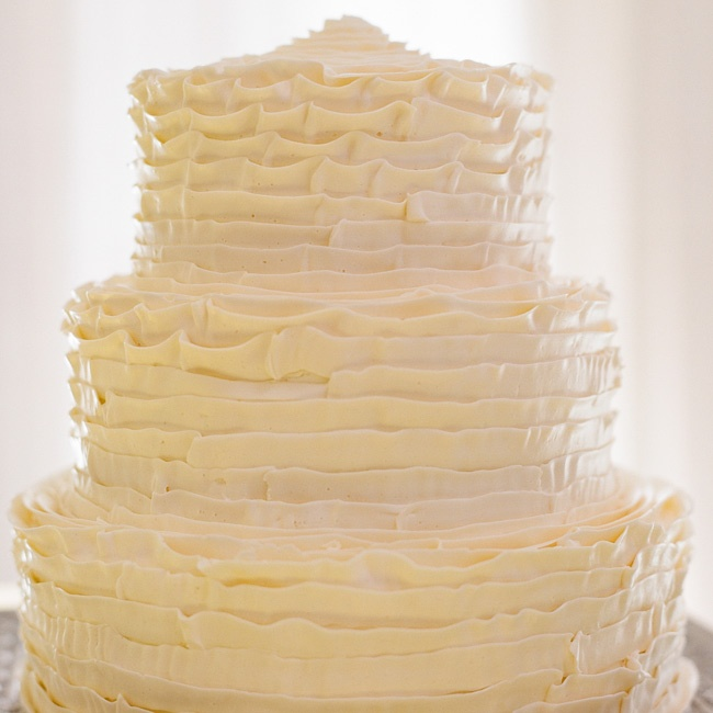 The modern three-tiered cake was frosted with white buttercream ribbons.