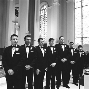 The men echoed Chris's look in traditional black tuxedos and bow ties.