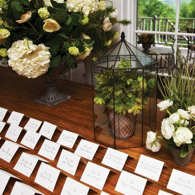 The white tented escort cards were displayed on a wooden table along with intentionally mismatched floral arrangements.