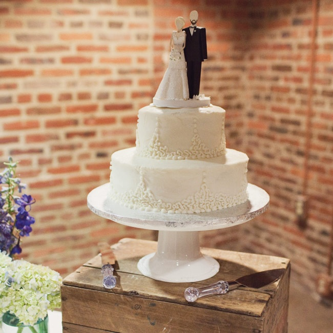 The simple white cake was displayed on a wooden crate. The paper topper was custom-made to resemble the couple.