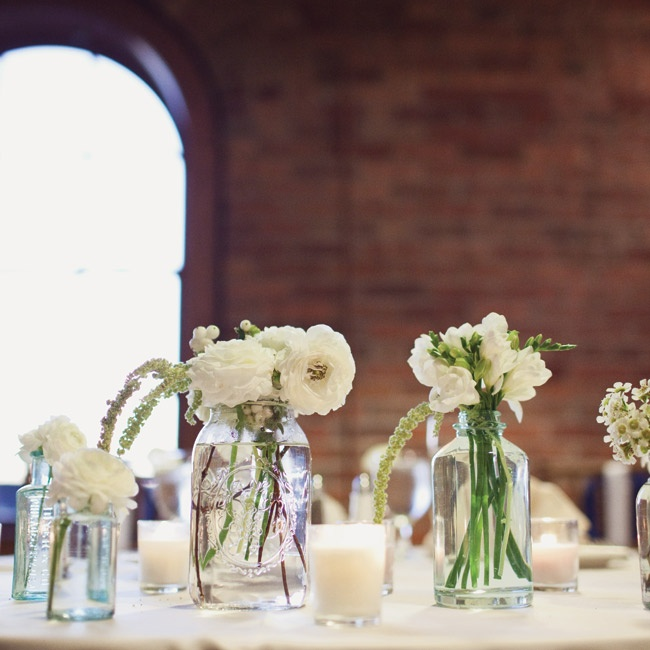 White blooms in assorted glass jars dotted the sweetheart table.