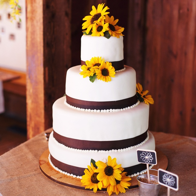 Using ribbon and fresh cut sunflowers, Laura's friend Tammy created the couple's earthy cake. Tammy's husband constructed the wooden base for the cake to rest on.
