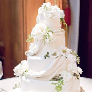 The four-tiered cake was decorated with fabric-like pleating and fresh white flowers and greens. To make it truly special, Anne