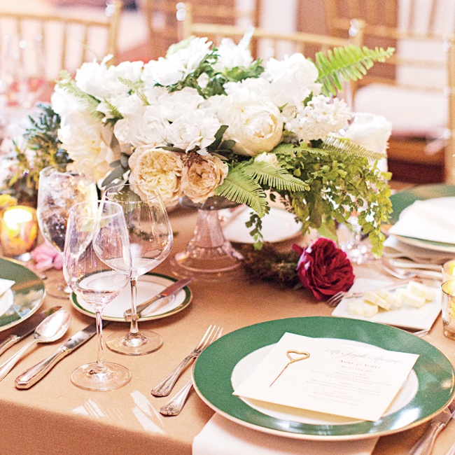 Lush white-and-green centerpieces gave the reception tables a garden-party feel, while beige linens and green-and-gold-rimmed china kept the look timeless.