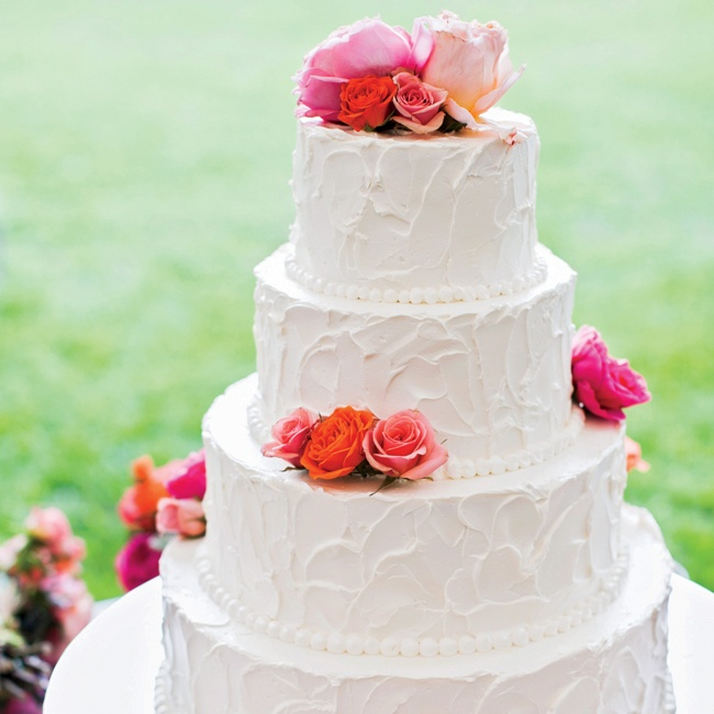 The four-tiered buttercream cake was finished with pretty pearl piping and brightly colored fresh roses.