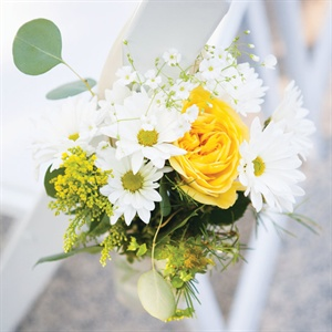 Bunches of yellow and white flowers hung from the chairs along the ceremony aisle.