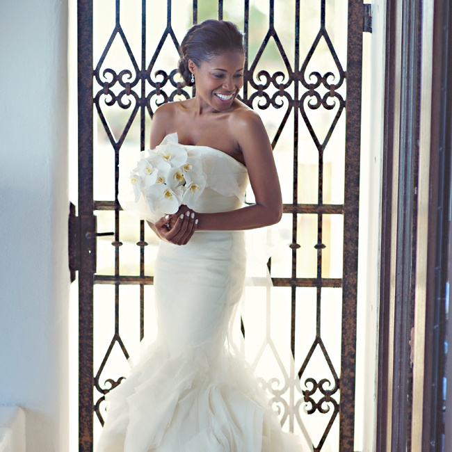 Meka wore a strapless Vera Wang dress with a silk organza overlay that she added during alterations. She finished her look with a laser-cut, raw-edged silk train.