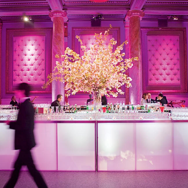 Tall cherry blossom centerpieces and pink lighting highlighted the reception space.