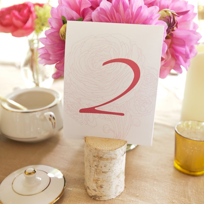 The peony design that was a unifying theme on the wedding paper served as the background to the table numbers, which were set in blocks of wood.