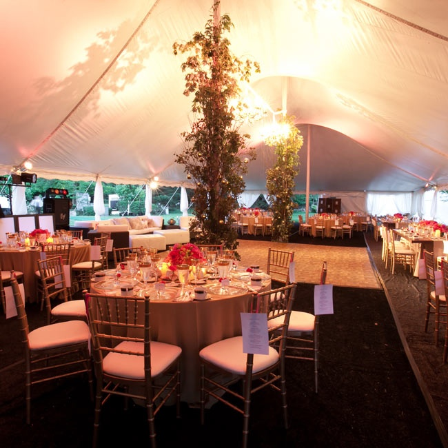 Birch branches wrapped around the poles that defined the dance floor, and dense, garden-style arrangements of pink flowers decorated the round tables.