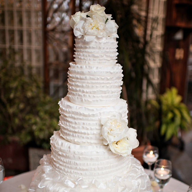 The top four tiers of the cake were covered in fondant ruffles, while the bottom layer featured ruffles made from sugar.